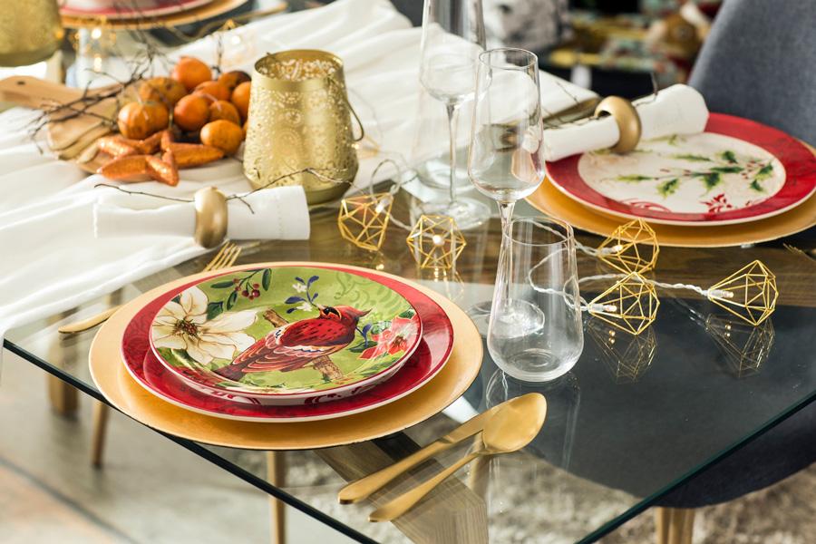 Mesa de vidrio con platos dorados y con pájaros y flores y cubiertos dorados