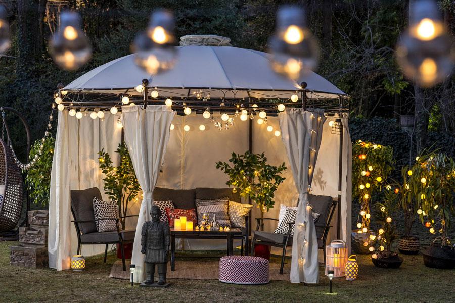 Jardín con pérgola y sillones exteriores con guirnaldas de luces