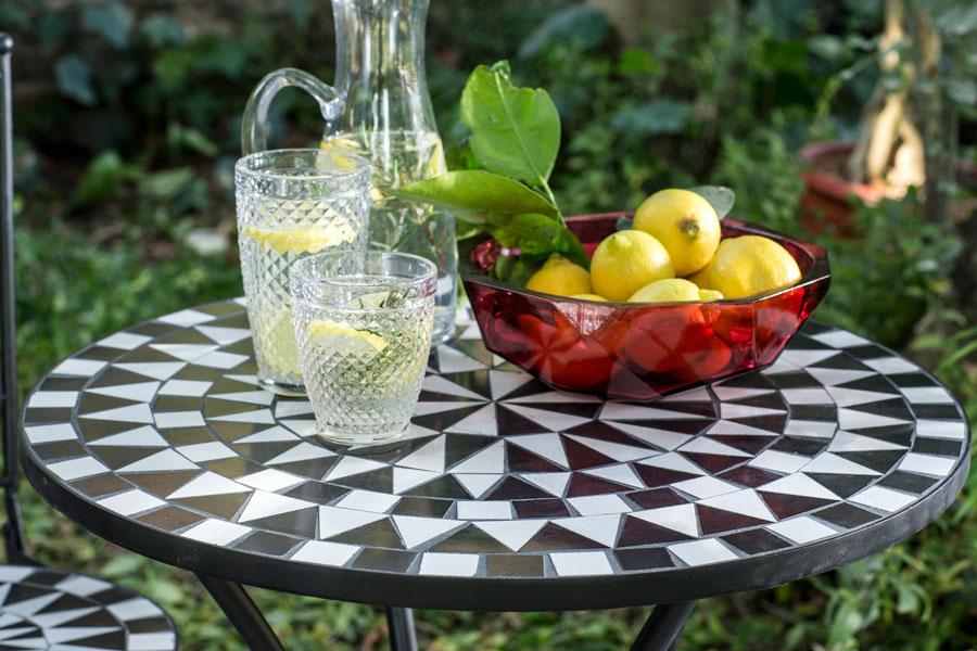 Mesa redonda de terraza con bowl con limones, jarra y vasos