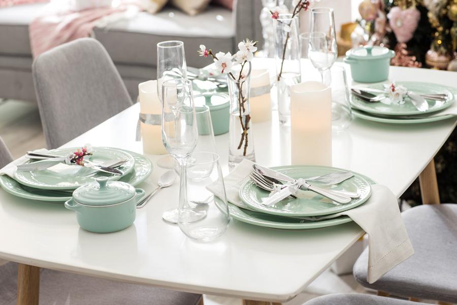 Mesa de comedor blanca con velas y platos en color verde agua