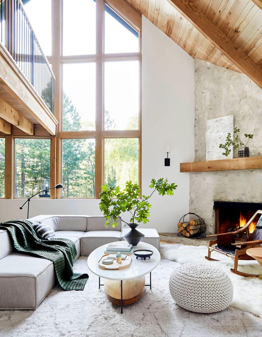 living con sofa gris, techos de madera, mesa de marmol y chimenea