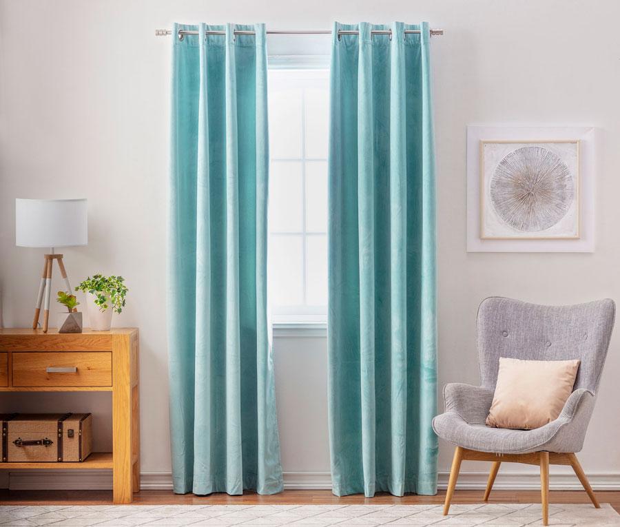 Ventana con cortina de terciopelo celeste y poltrona gris