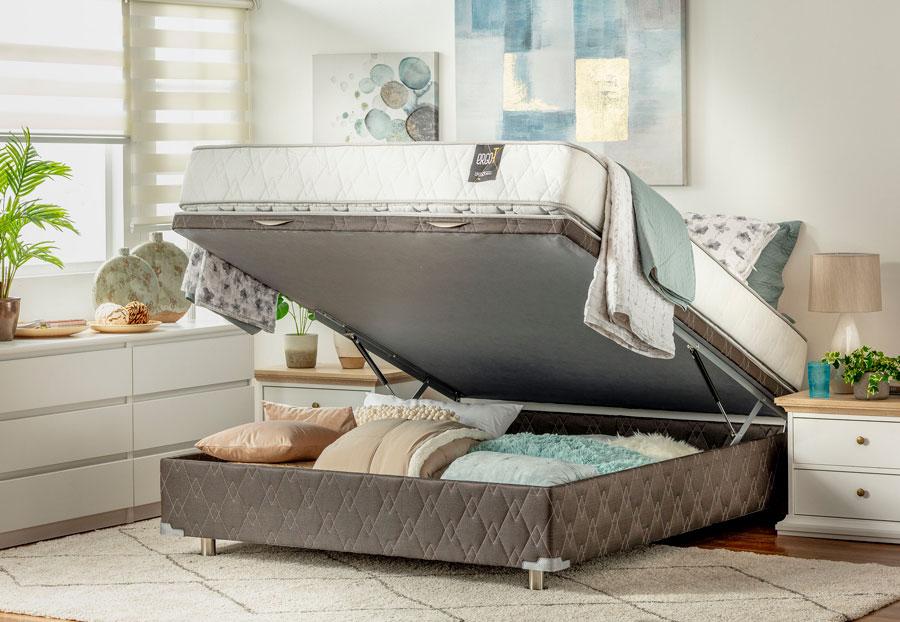 Dormitorio con cama que se levanta y ropa de cama guardada