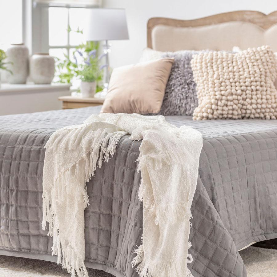 Dormitorio con colcha gris y manta beige sobre la cama