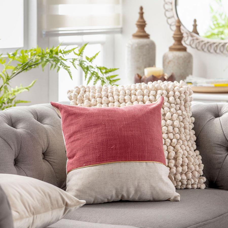 Sofa gris con cojin en tonos rojos y cojin de bolitas de lana