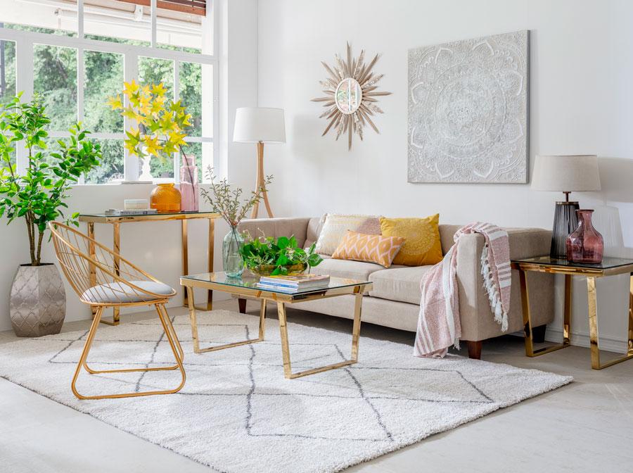 Living con alfombra beige, sofa beige y mesa y silla doradas