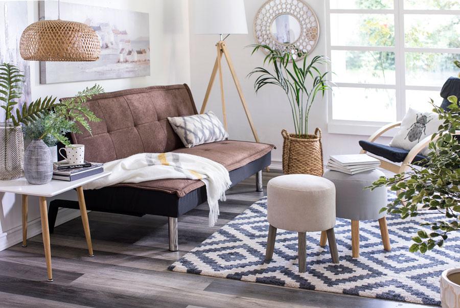 Living con futón color cafe, pouff, alfombra y lampara de mimbre