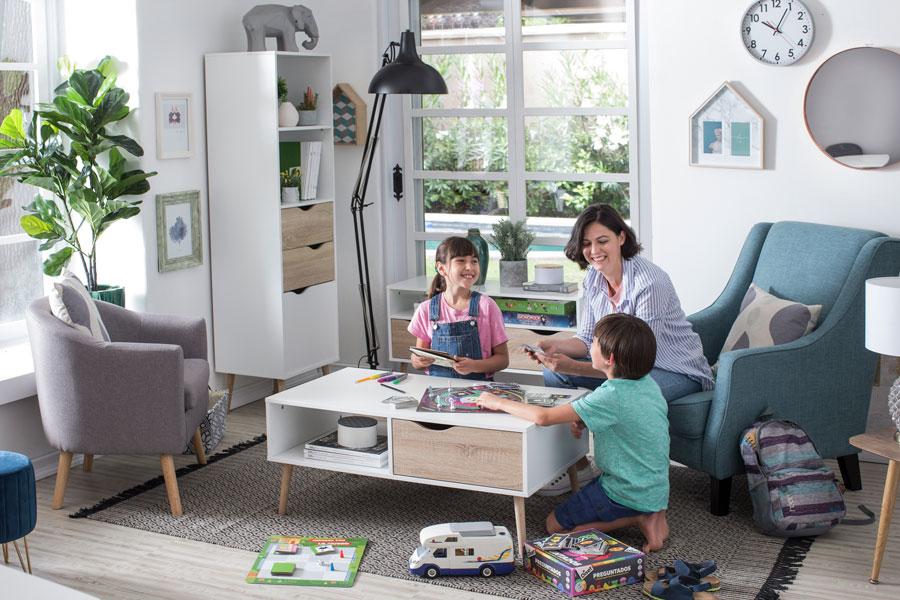 Living con mamá y dos hijos jugando juegos de mesa como idea para la decoración del día de la madre. La imagen tiene un enlace a la categoría Muebles de living de Sodimac.com
