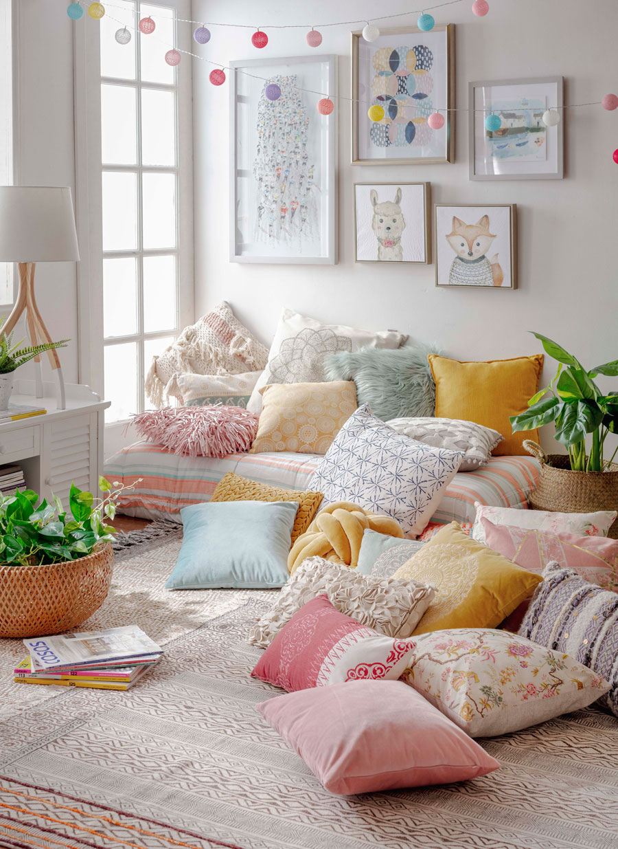 Living con cojines decorativos en el piso como decoración para el día de la madre con una tarde de películas. La imagen enlaza a la sección de Cojines decorativos de Sodimac.com