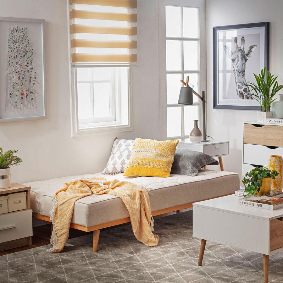 Living con futon beige, manta y cojines