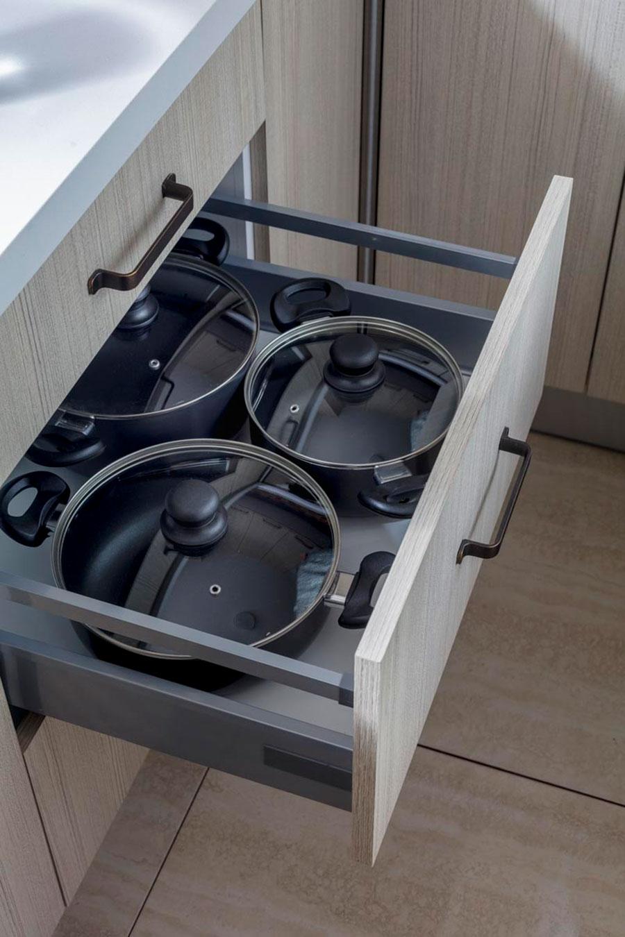 Mueble de cocina, con cajón abierto y batería de cocina