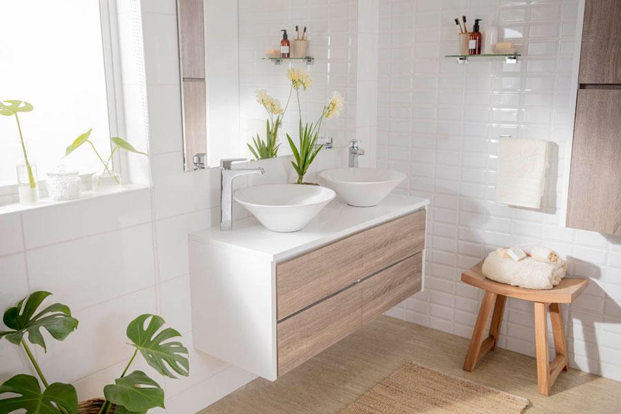 Baño con ceramicos blancos, y vanitory con madera