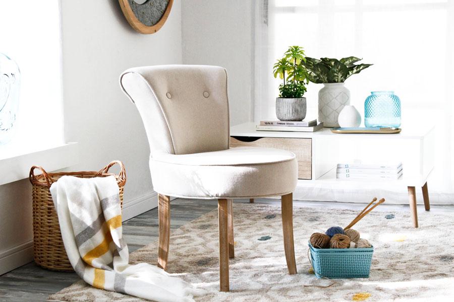 Poltrona beige sobre alfombra con canasto con tejido y manta