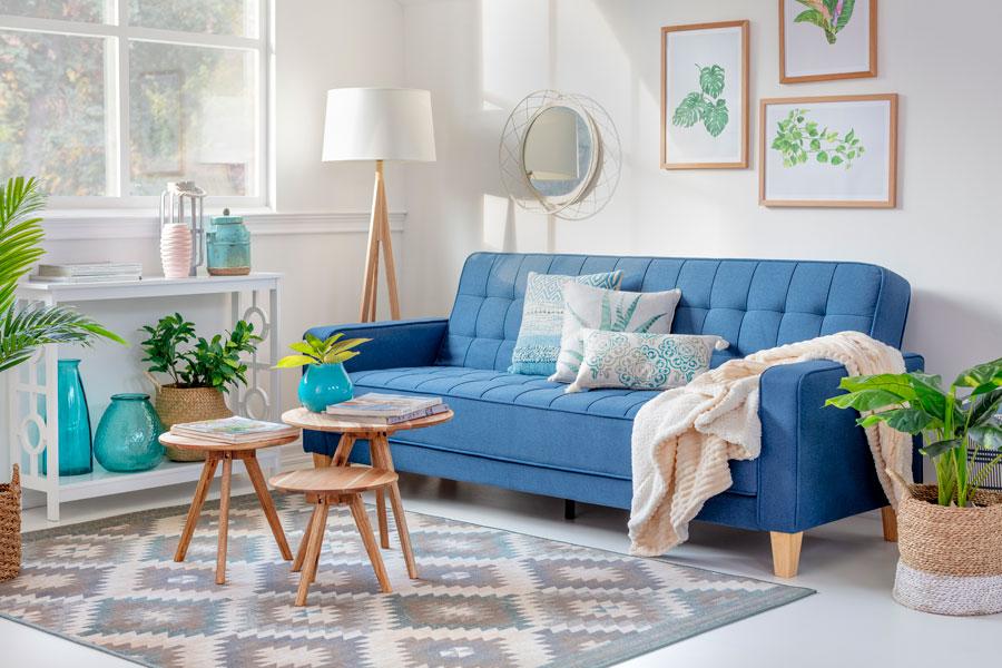Living con sofa azul, set de 3 meses redondas sobre alfombra