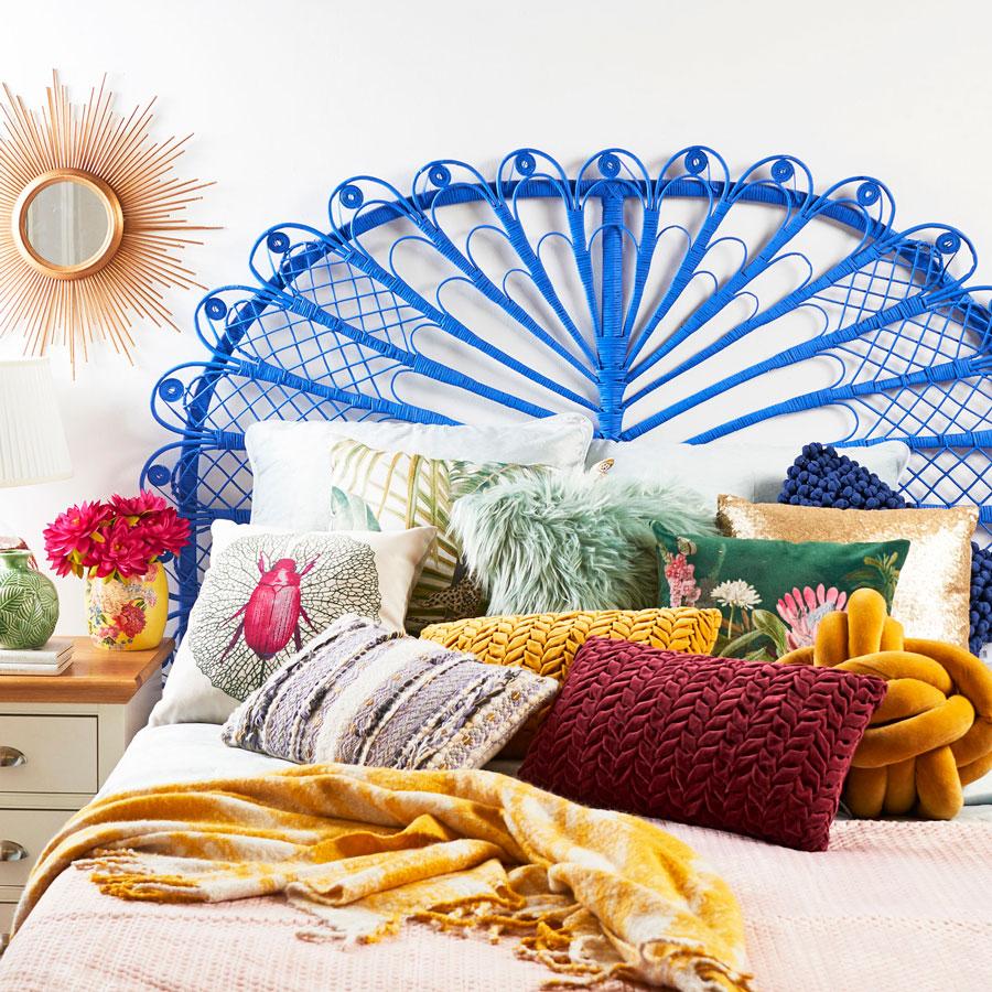 Dormitorio con respaldo de mimbre azul, y muchos cojines de distintos estilos, texturas y colores