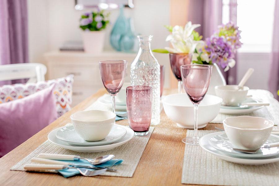 Mesa con vajilla blanca y copas color lila