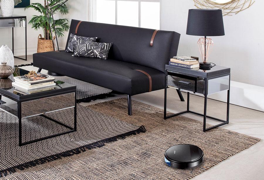 Living con futon negro y aspiradora robot sobre alfombra