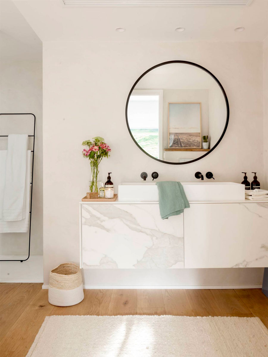 Baño con espejo redondo negro