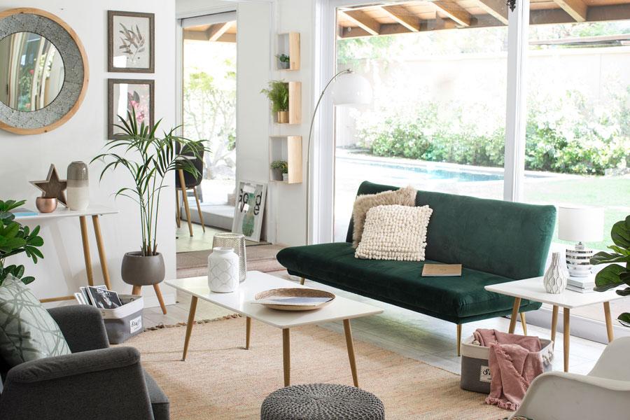 Living con futon verde y mesa de centro blanca con patas alargadas de madera