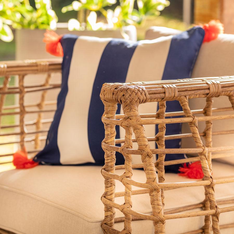Cojin de terraza rayado azul y blanco en sofa de rattan