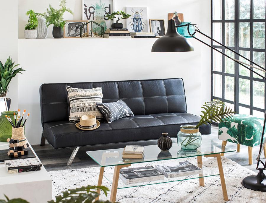 Living con futón negro y mesa de centro de madera y vidrio