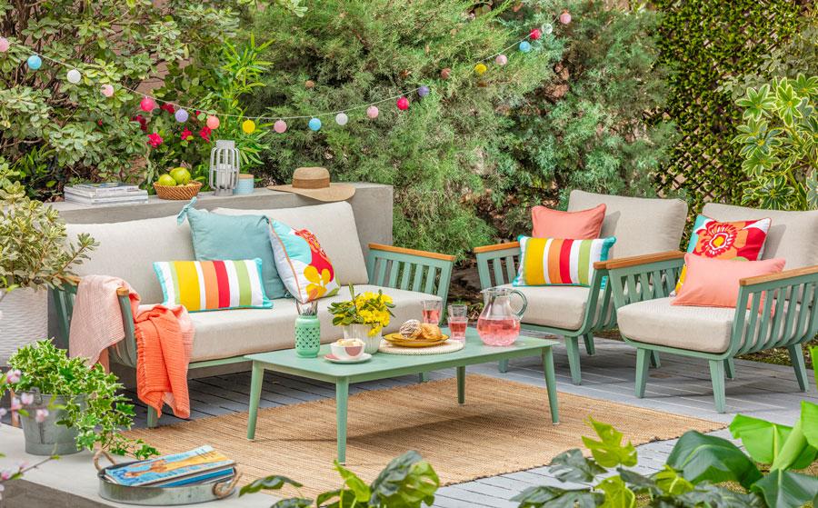 Living de terraza verde con cojines en tono coral