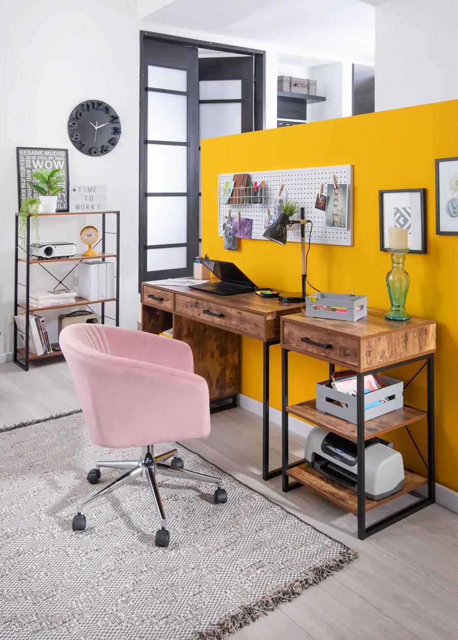 Escritorio de madera con muralla amarilla y silla rosa palo