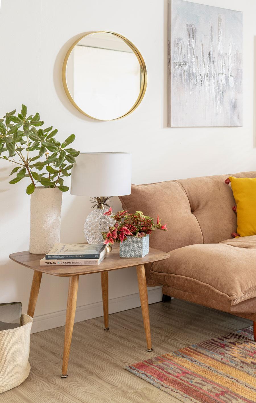 Detalle de living con mesa auxiliar de madera y patas largas y espejo redondo con marco dorado
