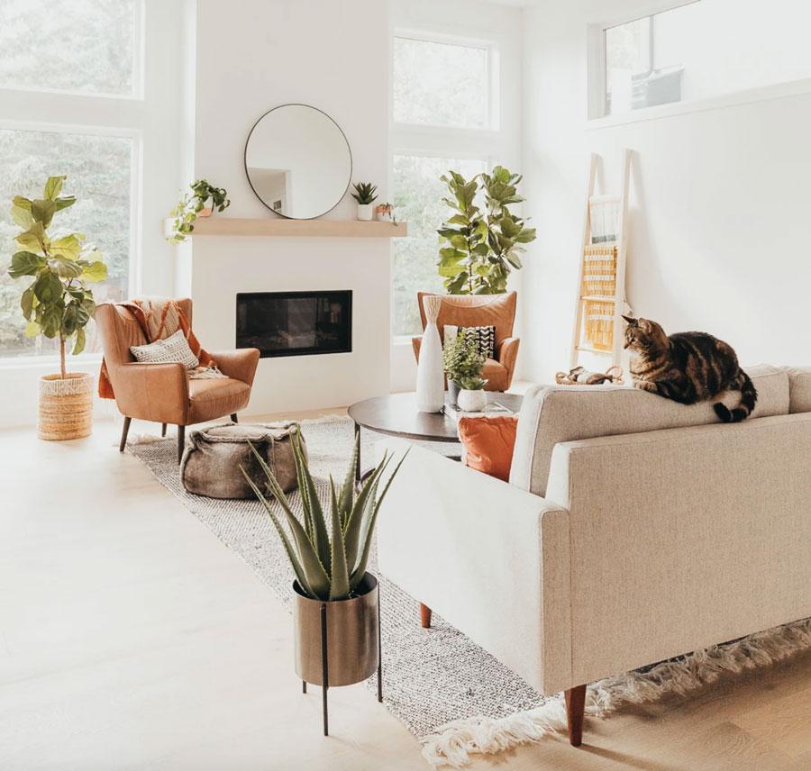 living de muros blancos y sofá en color beige y poltronas color café con muebles y complementos en grises y blancos