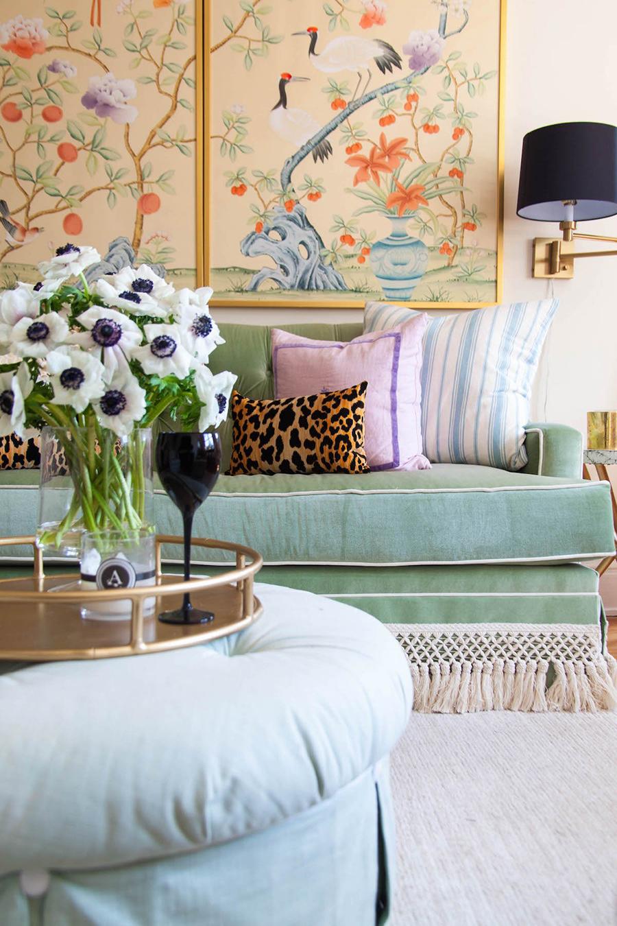 decoración ecléctica de living con un tríptico oriental de fondo y cojines de distintos estilos sobre sofá verde menta