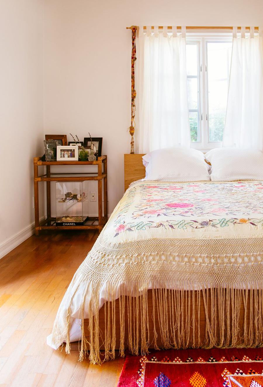 cama en dormitorio de colores clares con cobertor tipo mantón de manila