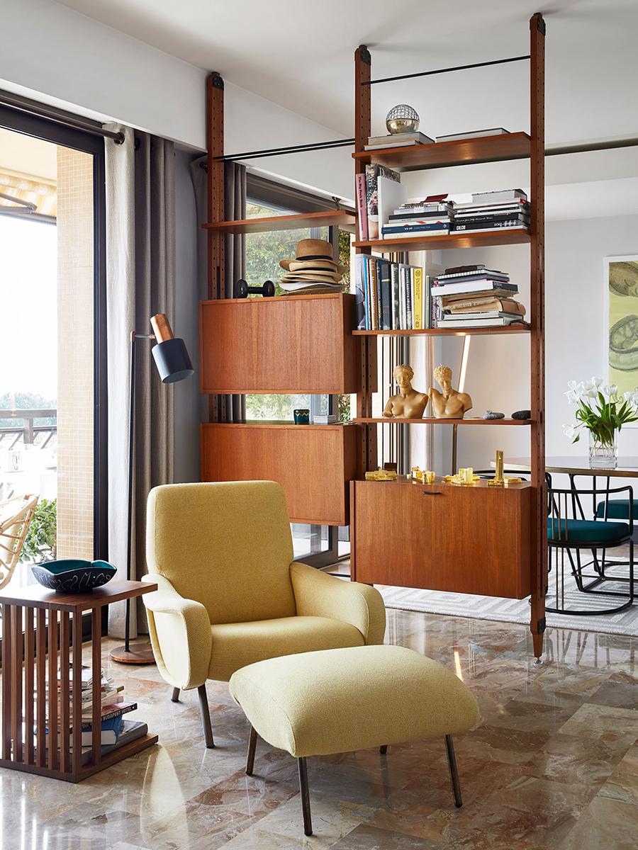 Decoración vintage moderno de living comedor, con sillón en tonos mostaza y reposapiés a juego, muebles de madera de diseños sencillos y comedor al fondo