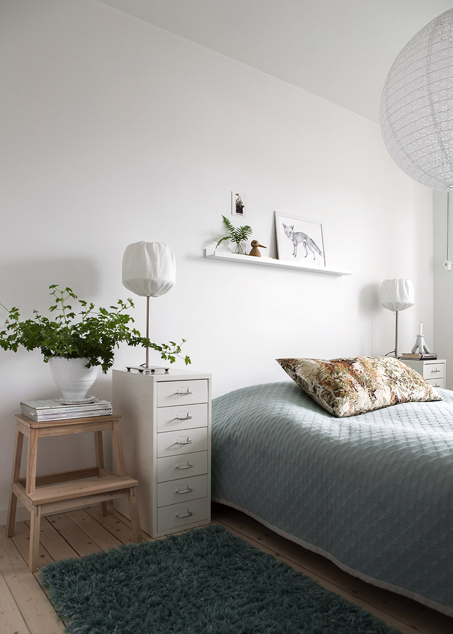 dormitorio de look nórdico con cama de plaza y media, velador cajonera blanca y lámparas de papel, colgante y de mesa.