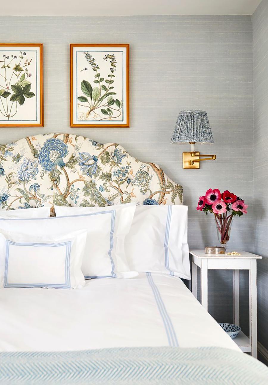gran cama de dormitorio con respaldo de motivos vegetales y cuadros de inspiración botánica. Acompaña mesilla de noche con florero con amapolas y una lámpara de apliqué con pantalla y tonos azules