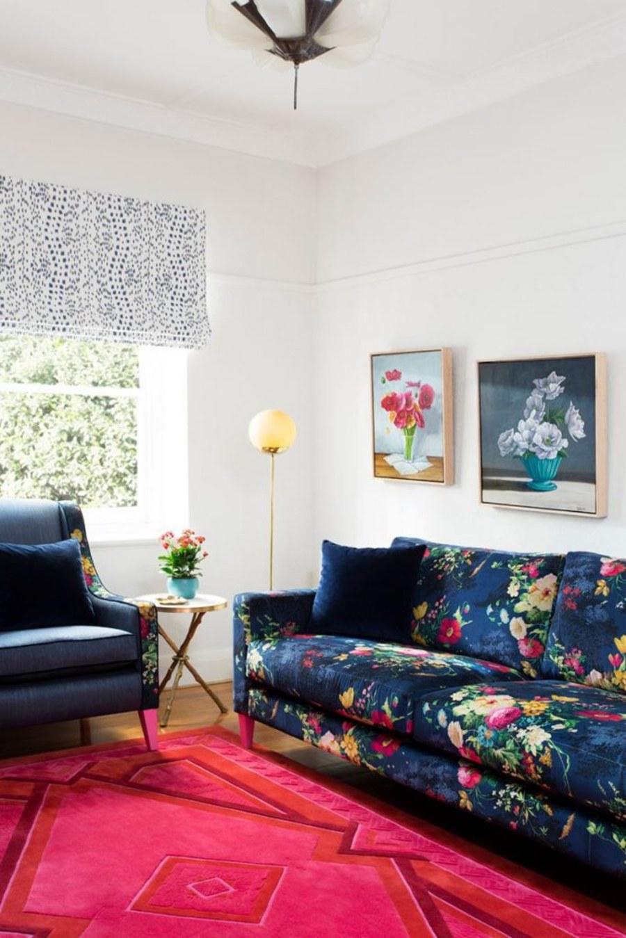 detalle de living estilo grandmillennial con sillón y sofá azul oscuro y estampados floreados junto a ventana con cortina tipo store y cuadros florales