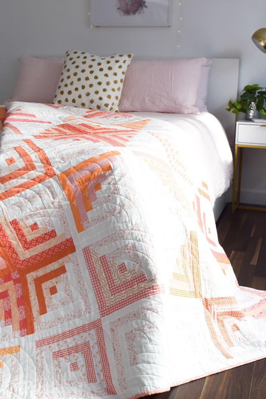 quilt con diseños geométricos en naranjo y rosado para decoración de de dormitorio
