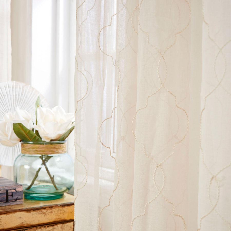 Una cortina de una tela semi transparente, color claro. La tela ligera la hace ver muy liviana.