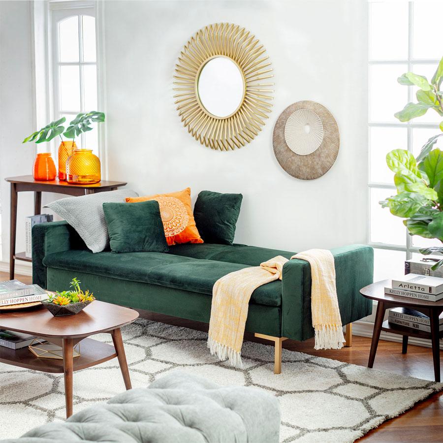 futón tipo chaise longue verde en un living decorado con tonos grises. Tiene cojines y una manta y algunos detalles decorativos de color naranjo