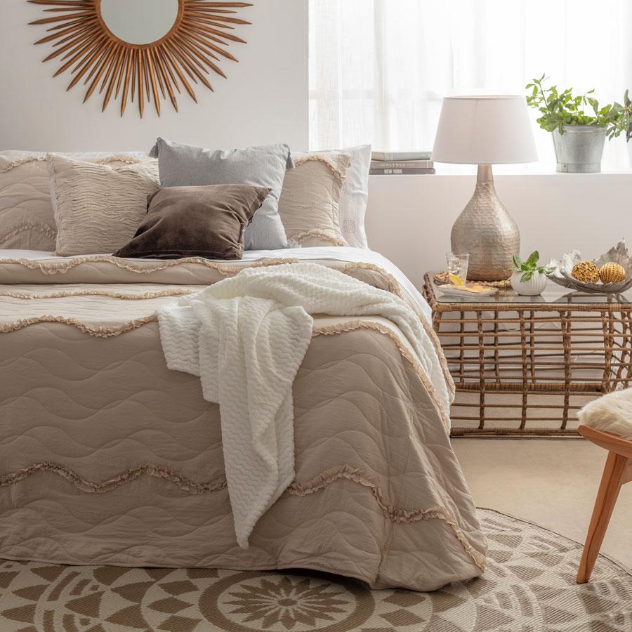 Dormitorio en tonos beige y madera, con ropa de cama en distintas tonalidades de gris y color cream, alfombra con tonos beige y crudos y silla, velador y un espejo con tonos madera. El dormitorio es compartido a la hora de vivir en pareja.