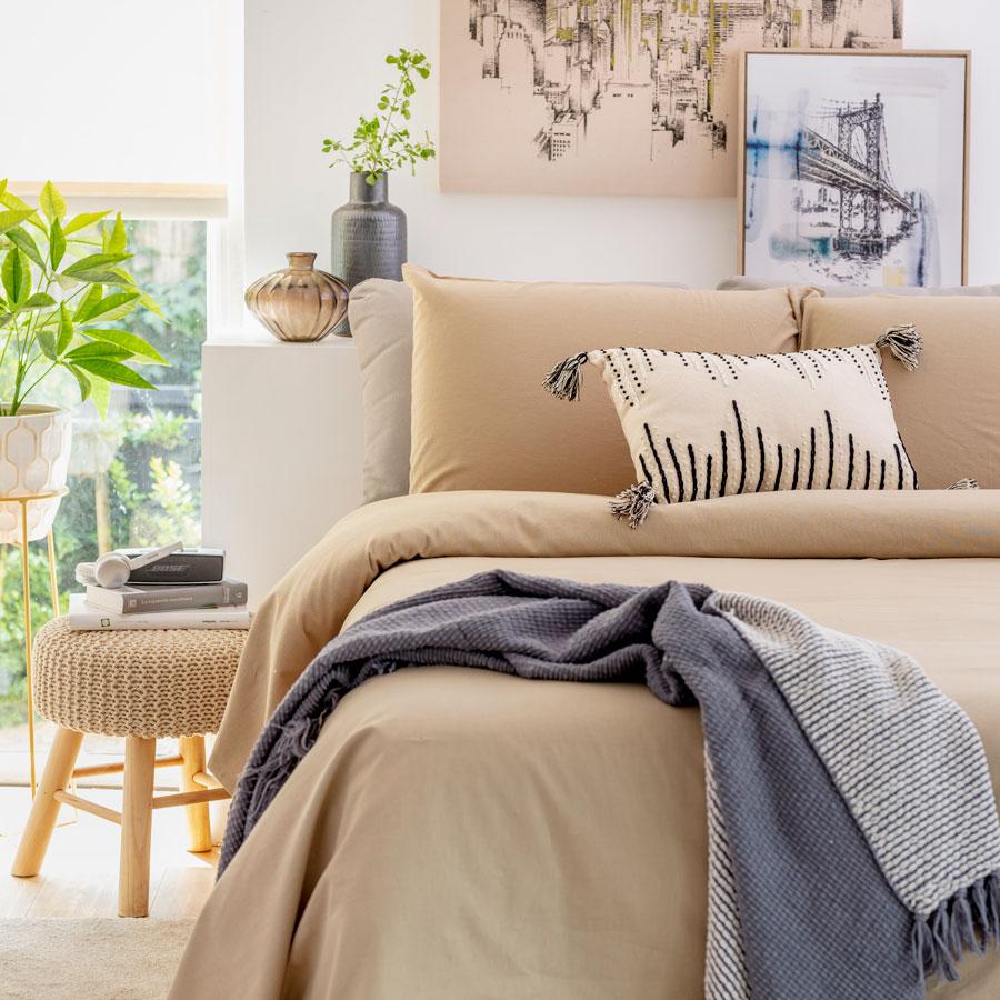 La ropa de cama utilizada en este dormitorio es de color liso. Se trata de un beige claro, que combina con los cojines decorativos, el arte del dormitorio, varios adornos y la banqueta.