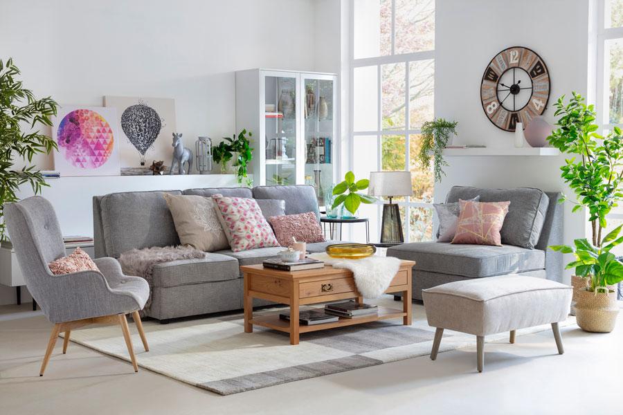 Un living muy acogedor, con cojines de colores sobre el sofá gris. Varios cuadros y adornos en las paredes y en toda la decoración.