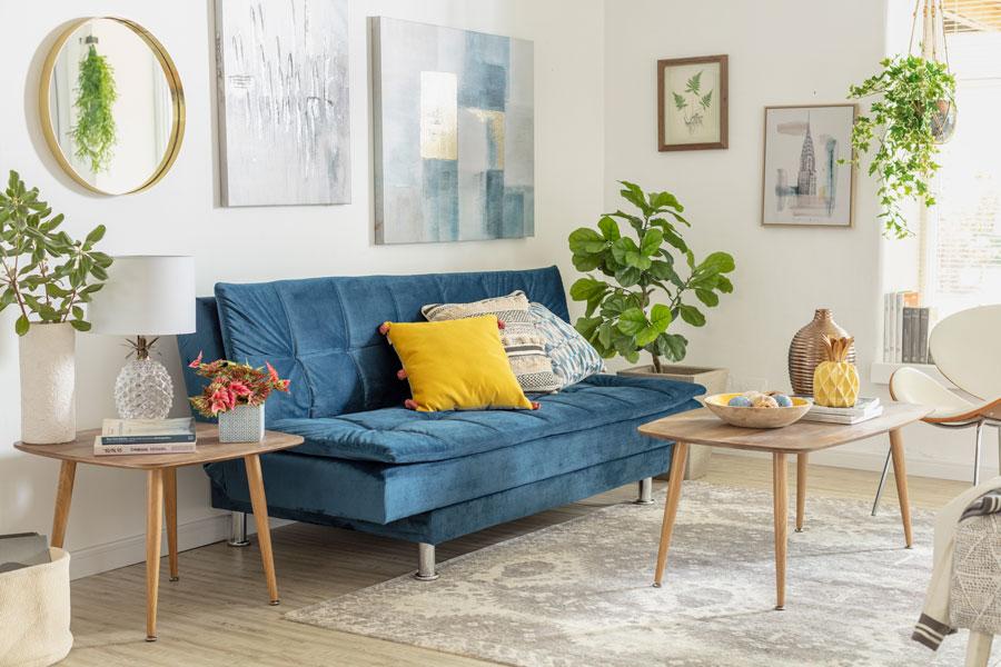 Futón azul de tapiz aterciopelado, situado en living con tonos claros y mesa de centro y lateral de madera clara con patas largas. Ambientado con plantas y cuadros