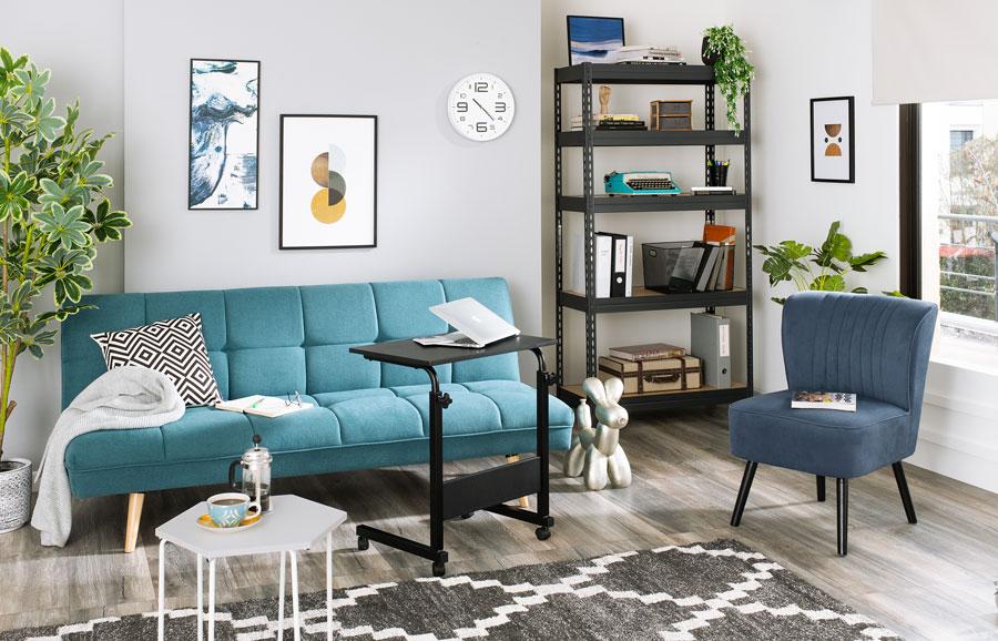 Futón turquesa con silla azul en una sala de estar decorada en blancos y grises, con alfombra con motivos geométricos y mesas auxiliares y una repisa