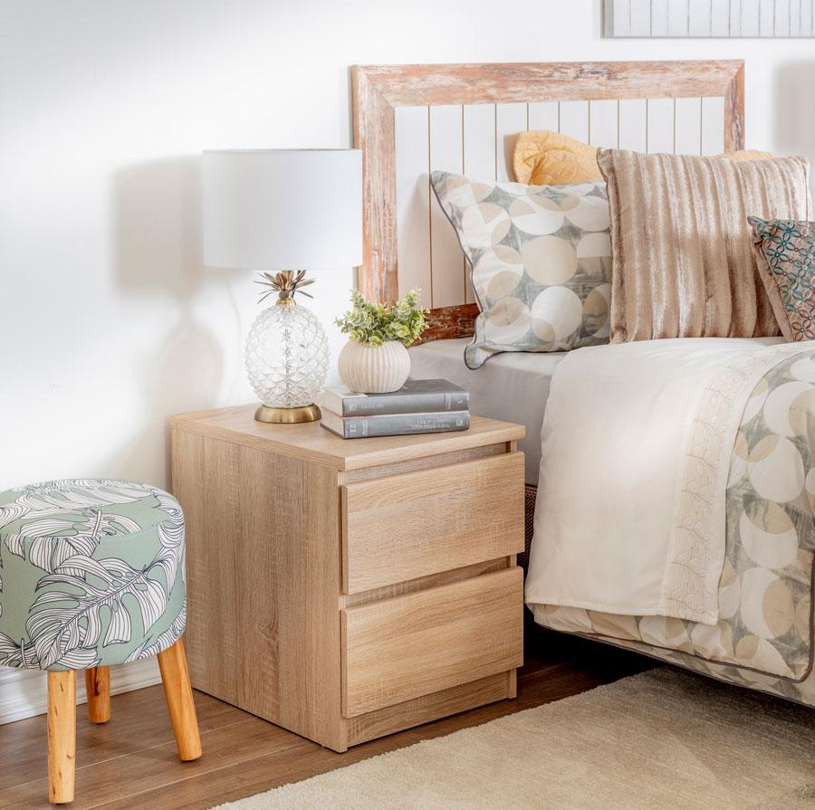 Un respaldo de cama de madera con diseño, que combina muy bien con los otros elementos del dormitorio, como velador y la ropa de cama.