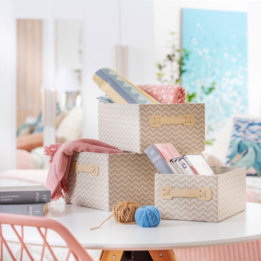 Varias cajas de organización para guardar elementos como textiles, libros o implementos de tejido. Tienen diseños geométricos y colores crema.