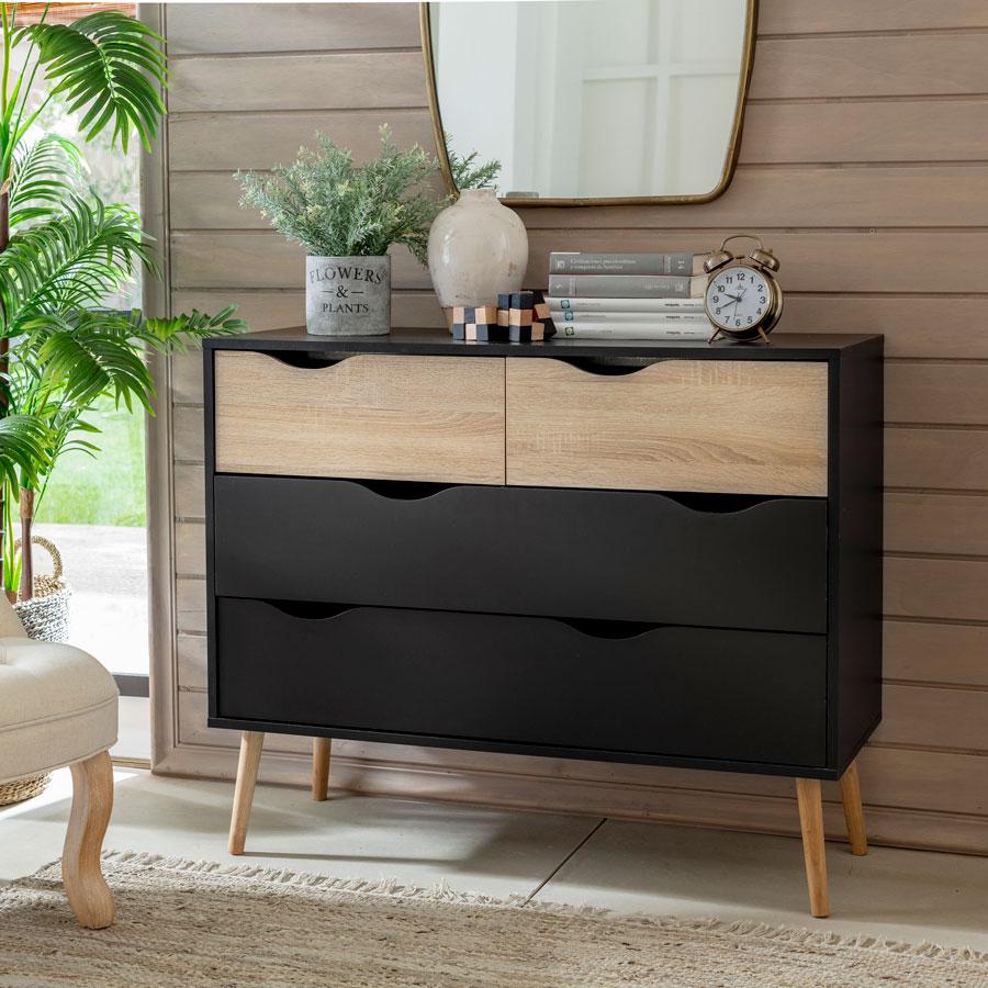 """Cómoda con patas separadas, en negro y color madera. La forma y disposición de sus patas de madera, hacen que la cómoda se vea """"flotando"""" en el ambiente, y da la ilusión de que el espacio es más amplio."""