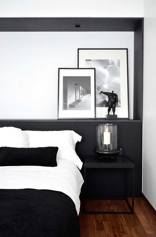 Un dormitorio en el que predomina la decoración en colores blanco y negro.