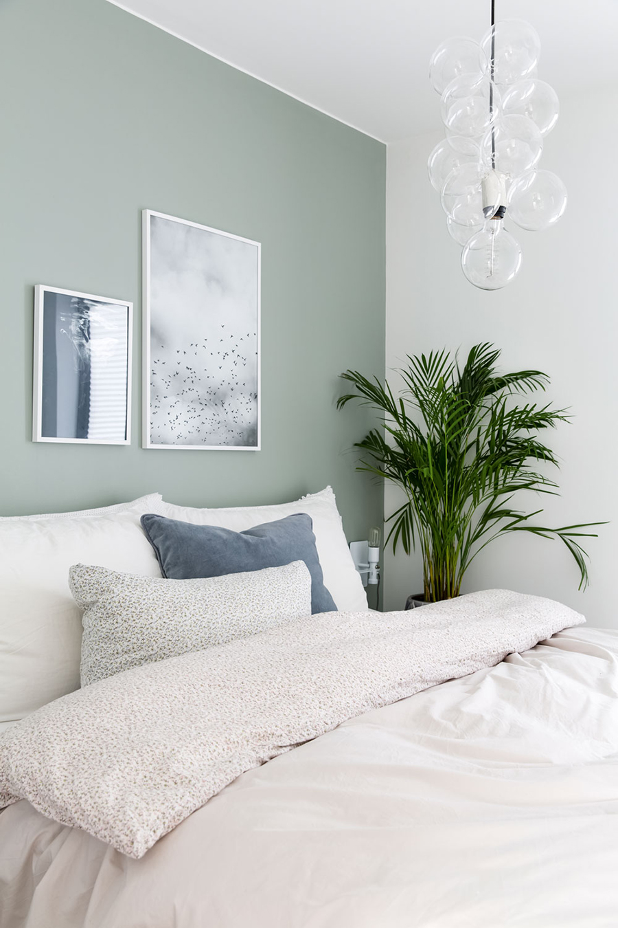 Dormitorio con ropa de cama blanca y una pared verde grisáceo muy claro, para que se vea más amplio e iluminado