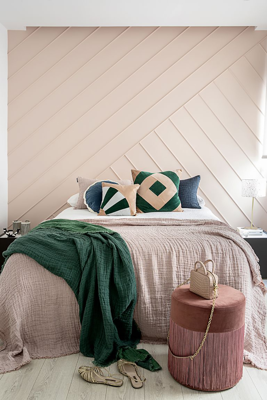 Dormitorio con pared adornada con molduras en líneas diagonales, formando un diseño.
