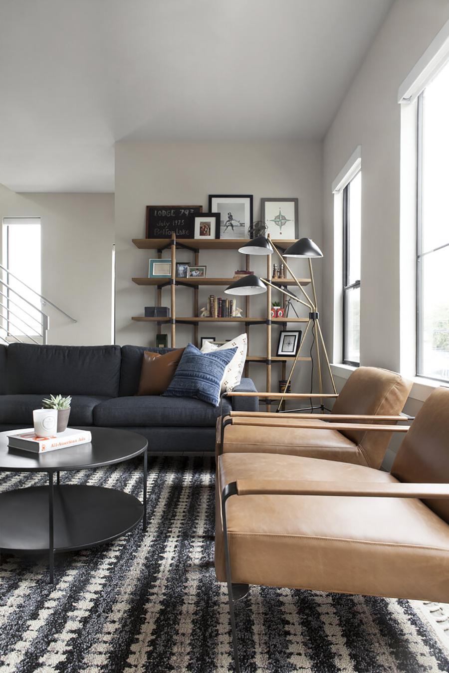 Un living de estilo ejecutivo urbano, con un gran sofá en gris azulado y dos poltronas en color camel. Una gran alfombra con motivos grises, estanterías de madera y una mesa de centro negra.